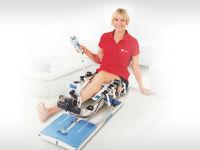 Женщина разрабатывает колено на Артромоте