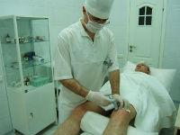 Врач делает укол в коленный сустав