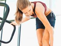 Девушка в спортзале трет ногу