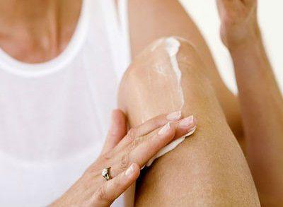 Женщина втирает крем в коленный сустав