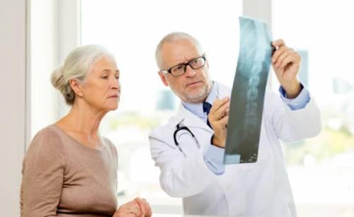 Врач показывает пациентке рентгенснимок позвоночника