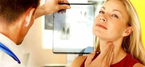 Врач обследует щитовидную железу