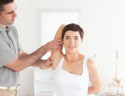 Врач осматривает плечевой сустав женщины