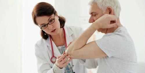 Врач осматривает локтевой сустав у пациента