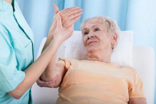 Врач сгибает локоть пациента