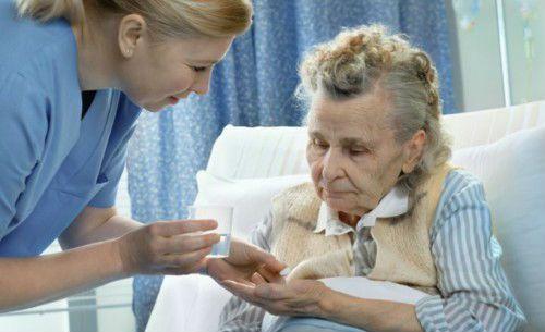 Пожилая пациентка принимает лекарство