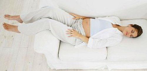 Беременная отдыхает лежа с приподнятыми ногами