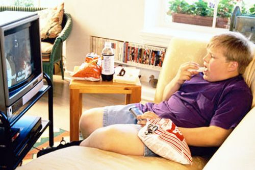 Жирный мальчик перед телевизором