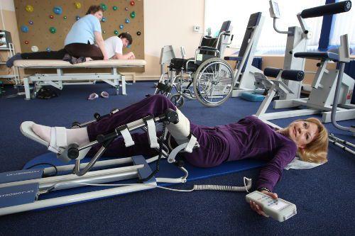 Женщина разрабатывает ногу на аппарате