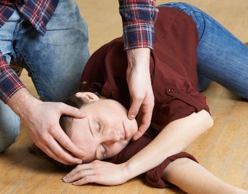 Женщина лежит на полу, ей поворачивают голову