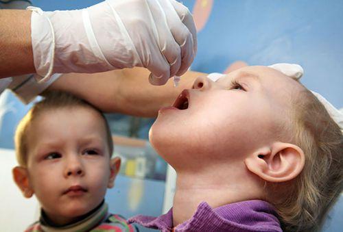 Ребенку капают вакцину от полиомиелита