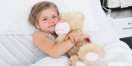 Ребенок в постели с мишкой