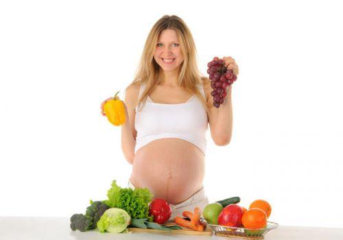 Беременная выбирает фрукты и овощи