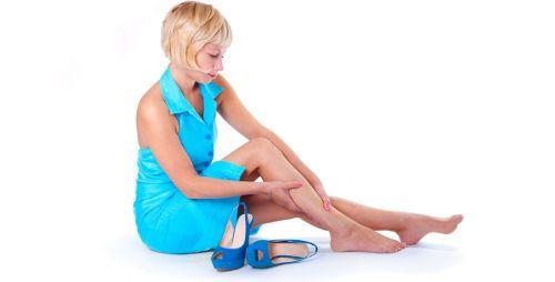 Женщина сняла туфли и трет ногу