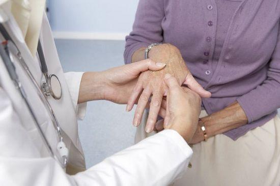 Осмотр пальцев рук врачом