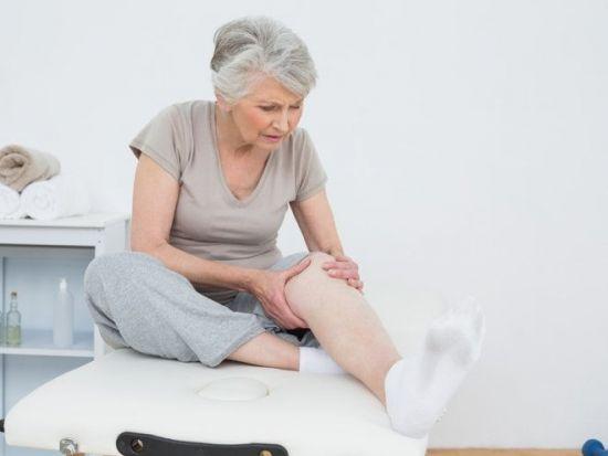 Женщина осматривает колено