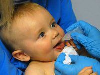 Ребенку в рот капают вакцину