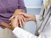 Врач осматривает кисти пациента